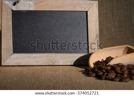 Coffee beans and empty blackboard lying on jute fabric / Coffee beans - stock photo