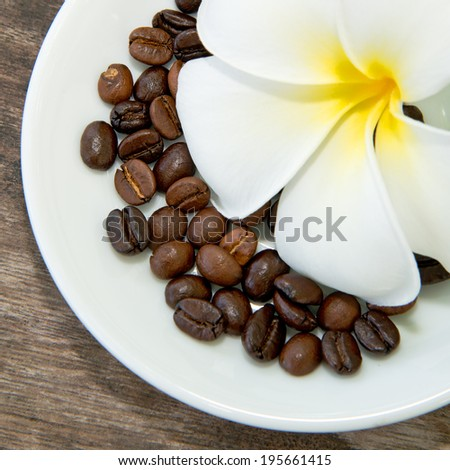 Coffee beans and flowers placed in the dish. - stock photo