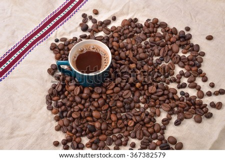 Coffee beans and green cup on textured background. copy space - stock photo