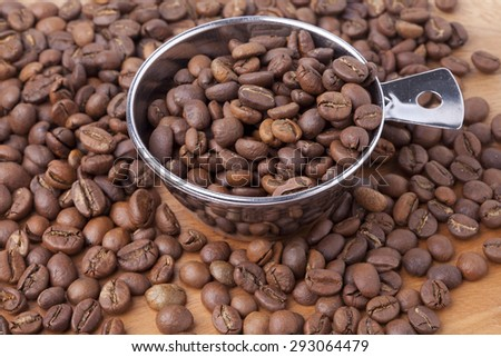 Coffee beans and measuring spoon on wood background / presentation / business