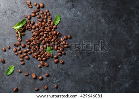 Coffee beans and mint leaves on dark stone table. Top view with copy space - stock photo