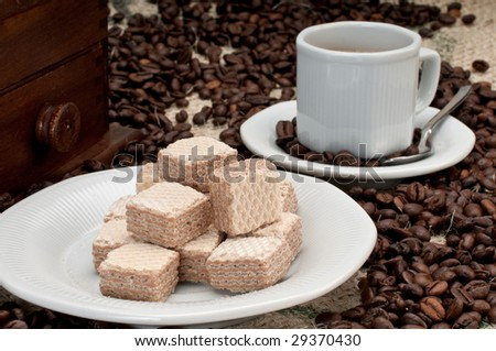 Coffee beans and wafer cookies with cup and grinder. - stock photo