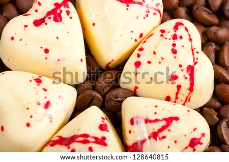 coffee beans and white chocolate heart candy. - stock photo