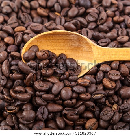 Coffee beans and wooden spoon isolated on white background. - stock photo