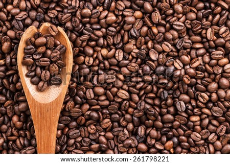 coffee beans and wooden spoon on the table background - stock photo