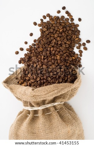 coffee beans are drop out of a burlap bag. - stock photo