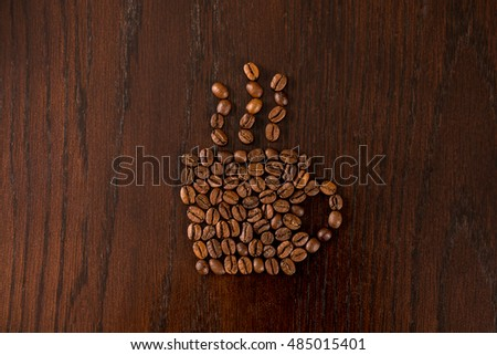 Coffee beans arranged into coffee cup.