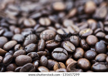 Coffee beans background with shallow depth of field and focus on foreground. - stock photo