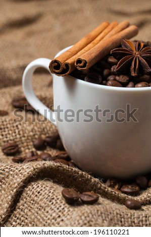 Coffee beans, cinnamon and aniseed in coffee cup. Close-up. - stock photo