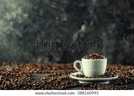 Coffee beans. Coffee cup full of coffee beans. Toned image. - stock photo