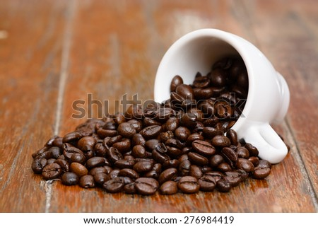 Coffee beans cup on old wooden table - stock photo