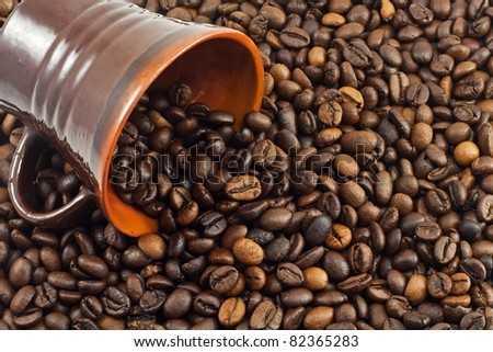 coffee beans falling from a coffee cup - stock photo