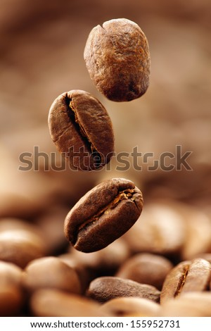 Coffee beans falling into a heap - stock photo