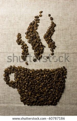 Coffee beans forming a cup on natural textile background, indicating coffee scent and flavor. - stock photo