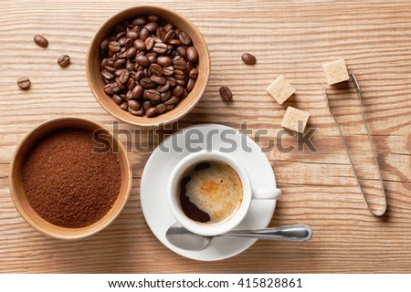 Coffee beans, ground coffee and cup of brewed coffee on rustic wooden table with sugar tongs, cane sugar cubes and coffee beans, view from above - stock photo