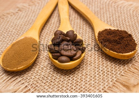 Coffee beans, ground coffee and instant coffee on wooden spoon lying on jute burlap - stock photo