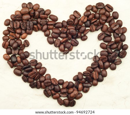 Coffee beans heart on  paper background - stock photo