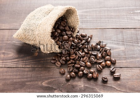 coffee beans in a bag on wooden background  - stock photo