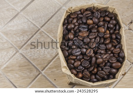 Coffee beans in a brown paper bag on wooden background.