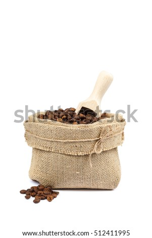 Coffee beans in a canvas bag with a wooden scoop isolated on white background.