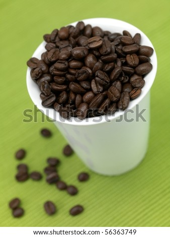 Coffee beans in a cup isolated against a green background - stock photo