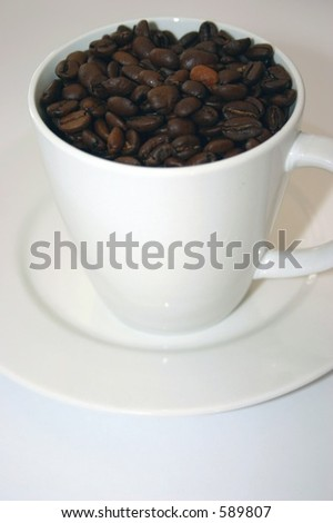 Coffee Beans in a cup on saucer - stock photo