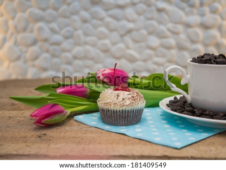 Coffee beans in a cup with pink tulips and cake on wooden table  - stock photo