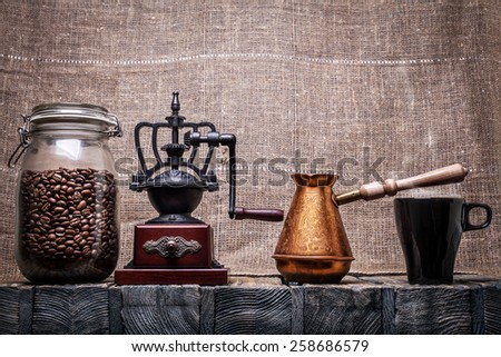 Coffee beans in a glass jar, coffee grinder, a coffee pot, a mug - stock photo