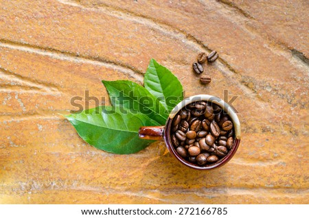 Coffee beans in a mug with leaves top view - stock photo