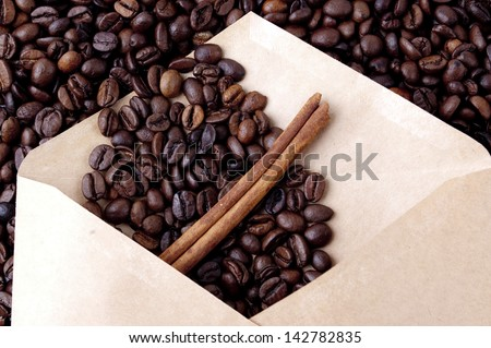 coffee beans in a paper envelope with a stick of cinnamon - stock photo