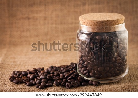 Coffee beans in a sack over textile background - stock photo