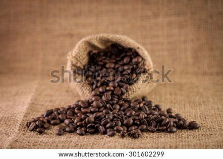 Coffee beans in a sack over textile background, pouring coffee beans - stock photo