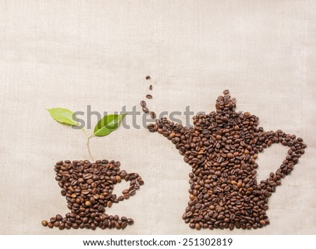 Coffee beans in a shape of coffee cup and coffee beans in a shape of coffee pot, green leaf on a sackcloth - stock photo