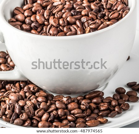 Coffee beans in a white coffee cup