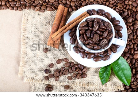 Coffee beans in a white cup on canvas. - stock photo