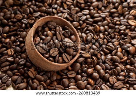 Coffee beans in a wooden bowl for storage on scattered coffee beans - stock photo