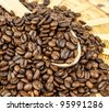 Coffee beans in a wooden spoon and as a background. - stock photo