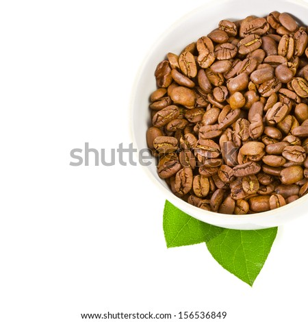 coffee beans in aa broad white bowl decorated with green leaves  isolated on white background - stock photo