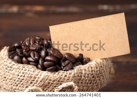 Coffee beans in bag and paper note for text on wooden table - stock photo