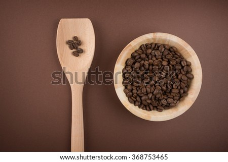 Coffee beans in bowl on brown background - stock photo