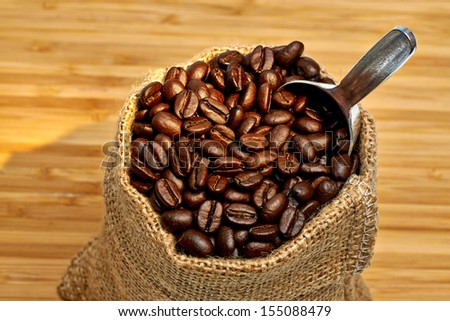 Coffee beans in burlap bag on wooden background with evening light - stock photo