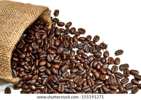 Coffee beans in burlap bag spread to white background - stock photo