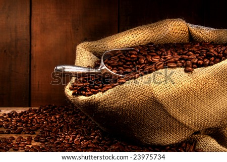 Coffee beans in burlap sack with antique wood background - stock photo