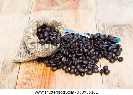 Coffee beans in burlap sack with spoon. - stock photo