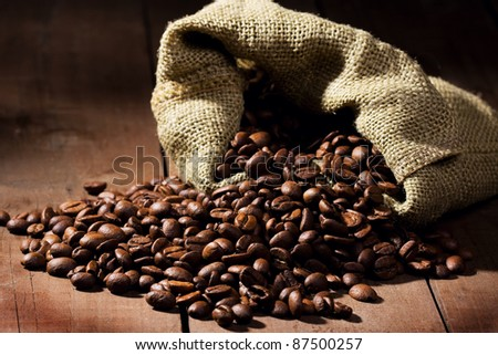 Coffee beans in canvas sack on wooden table