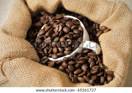 coffee beans in canvas sack with white cup