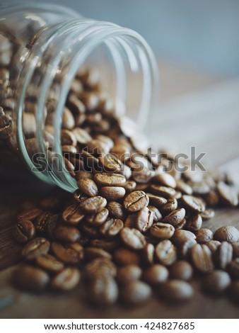 coffee beans in coffee bottle close up to coffee beans in vintage color tone , for coffee poster , coffee presentation ,coffee website , coffee menu , coffee photo in coffee shop ,coffee advertising - stock photo