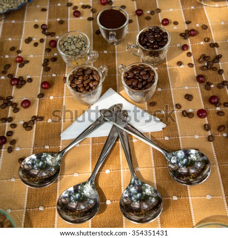 Coffee beans in glass and scoop on table. - stock photo