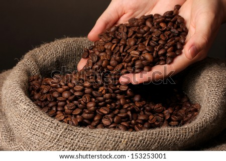 Coffee beans in hands on dark background - stock photo