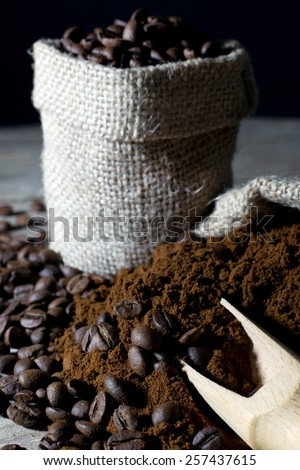 Coffee Beans in Jute Bag and Ground Coffee with Wooden Scoop Closeup, Black Background - stock photo
